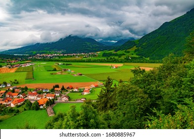 Stunning view of Sarine Valley from Gruyeres castle viewpoint. Fribourg Alps on background. Picturesque clouds. Gruyeres, Switzerland