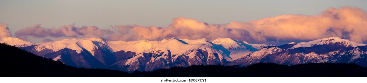 Stunning view of a snow capped mountain range during a beautiful sunset.
