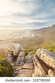 Stunning view through boulders and wooden footpath to ocean and mountains on golden sunset near Cape of Good Hope, South Africa