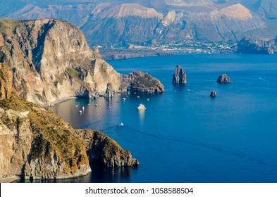 Stunning view of Valle Muria beach in Lipari and the Faraglioni. In the background the crater of Vulcano Island. Aeolian islands, Sicily