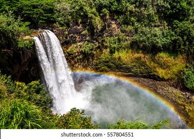 Stunning view of Wailua Waterfall near the island capital Lihue on the island of Kauai, Hawaii. Wailua Falls is a 173 foot waterfall that feeds into the Wailua River. Beautiful rainbow visible.