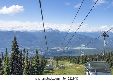 Stunning views of the distant mountains and valley below can been seen traveling down the chair lift on Blackcomb Mountain in Whistler British Columbia.
