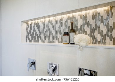 Stunning walk-in shower features white tile surround, shower niche  fitted with mosaic gray tiles. Northwest, USA