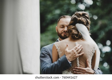 Stunning wedding couple dressed in classy style poses on the old porch under green trees