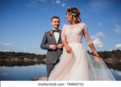 Stunning wedding couple with red flowers poses on the wooden bay under blue sky