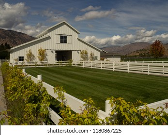 Stunning white barn and white fenced area of lush green grass in countryside