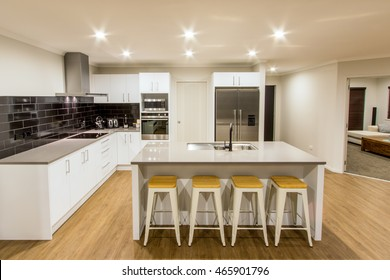 A stunning white modern kitchen with stone bench tops and wooden flooring