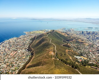 Stunning wide angle aerial drone view of Signal Hill and the suburbs of Mouille Point and Green Point with the stadium seen from above the summit of Lion's Head mountain in Cape Town, South Africa.