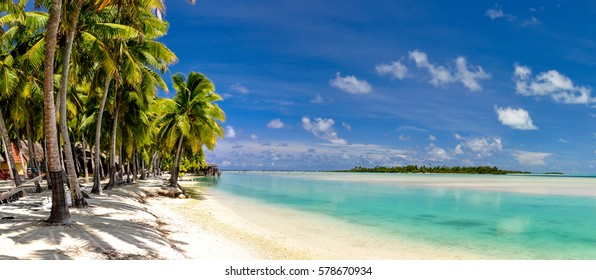 Stunning wide angle view of a beautiful beach on the remote island of Aitutaki, north of the main island Rarotonga, Cook Islands. White sand beach, shallow water, palm trees and a bungalow resort.
