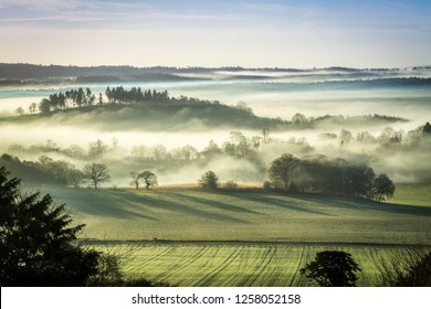 Stunning winter morning scene at Newland's Corner in the North Downs with fog in the valley. Countryside landscape in the Surrey Hills Area of Natural Beauty, UK.