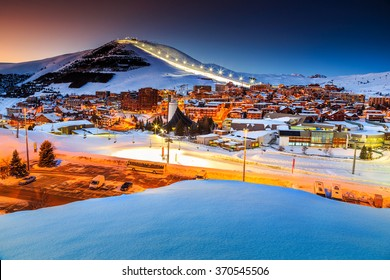 Stunning winter sunset landscape and ski resort with typical alpine wooden houses in French Alps,Alpe D Huez,France,Europe