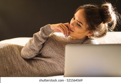 Stunning woman laying on a bed with laptop thinking about something - Attractive pretty girl in her bedroom working on her computer