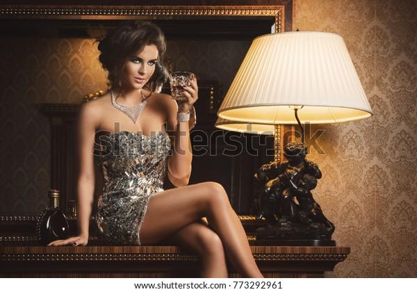 Stunning woman wearing beautiful shiny dress with a glass of cognac
