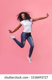 Stunning young african girl jumping over pink studio background