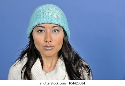 Stunning young Asian woman in winter themed photo - blue knit cap, blue makeup, and blue background - cold.