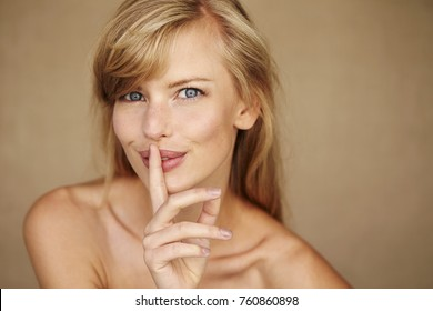 Stunning young blond woman with finger on lips, portrait