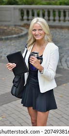 Stunning young blonde business woman in park - with notepad, coffee mug, and briefcase