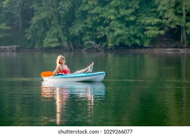 Stunning young blonde Caucasian woman rests in her kayak on a lake that is still