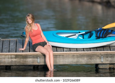 Stunning young blonde Caucasian woman rests during sunset on a small wooden boat dock wth her kayak behind her