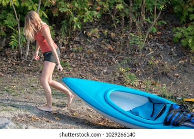 Stunning young blonde Caucasian woman drags her small boat (kayak or canoe) ashore after rowing