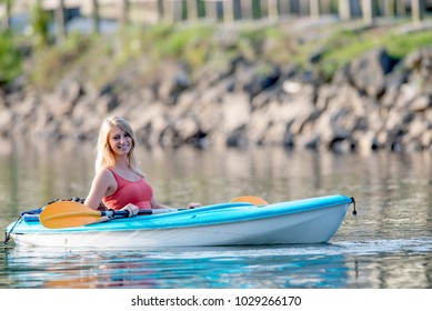 Stunning young blonde Caucasian woman paddles in a canoe on a still lake