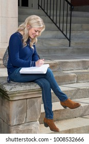 Stunning young blonde college student on campus in blue sweater and jeans sits and studies near building entrance