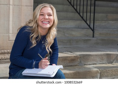 Stunning young blonde college student on campus in blue sweater and jeans laughs as she sits and studies near building entrance