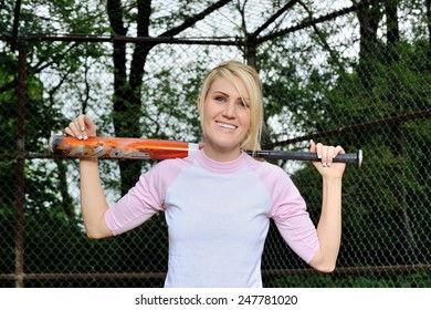 Stunning young blonde female softball player in pink and white baseball jersey shirt - holding bat over shoulders