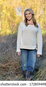 Stunning young blonde woman in beige colored sweater, blue jeans, and boots walking through field in autumn