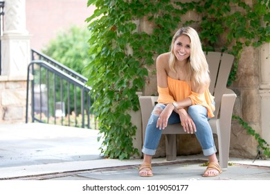 Stunning young blonde woman laughs as she sits in a chair on a front porch - ivy covered wall behind her