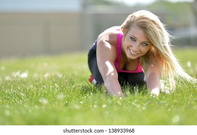 Stunning young blonde woman in pink sports bra stretches in the grass of an outdoor track
