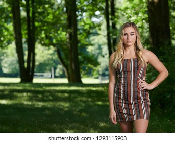 Stunning young blonde woman in summer dress standing in shady area of park