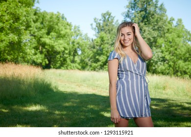 Stunning young blonde woman in summer dress standing in shady area of park in blue dress - open field behind her