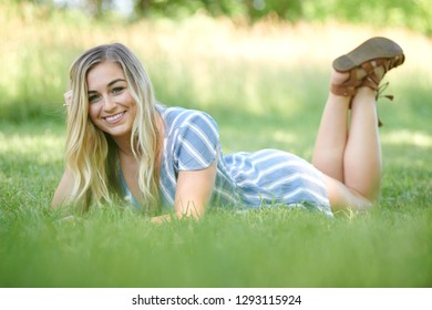 Stunning young blonde woman in summer dress laying on stomach in grass in shade