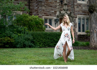 Stunning young blonde woman in white floral print dress poses for portraits in front of mansion home - fashion