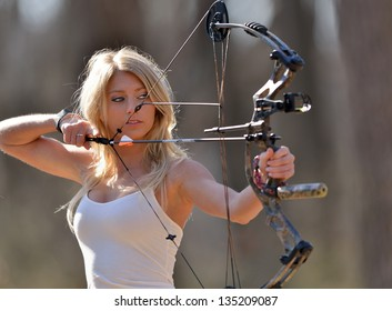 Stunning young blonde woman in white tank top and jeans preparing to shoot a compound bow - archery - aiming