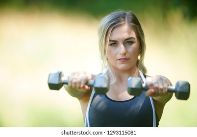 Stunning young blonde woman working out in summer heat - doing arm extensions - fitness