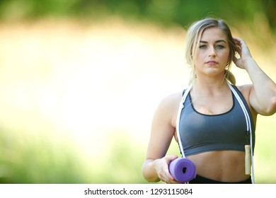 Stunning young blonde woman working out in summer heat - jump rope holding yoga mat - fitness