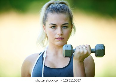 Stunning young blonde woman working out in summer heat - doing bicep curl - fitness sweat glistening on skin