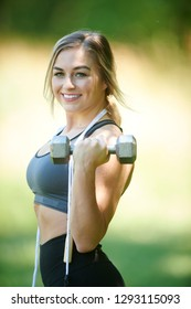 Stunning young blonde woman working out in summer heat - doing bicep curl - fitness