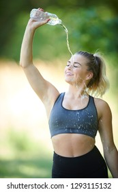 Stunning young blonde woman working out in summer heat - pouring water over head to cool down - fitness sweat glistening on skin