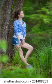 Stunning young brunette model standing in green woods - country or rural portrait - smiling