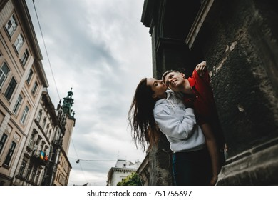 Stunning young couple poses before beautiful old building