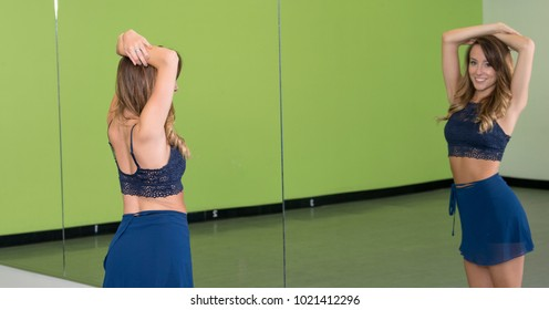 Stunning young female dancer in blue dance outfit in dance studio