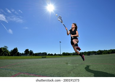 Stunning young female lacrosse player shooting as she leaps in the air, sunshine directly overhead - motion