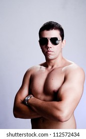 Stunning young man, with a very serious expression, appealing as the bad guy. The man is wearing sun glasses and his muscles are visible. A dramatic lighting has been used.