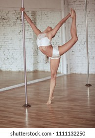 Stunning young slim woman in white clothes  performs pole dance and shows her fit figure in the studio