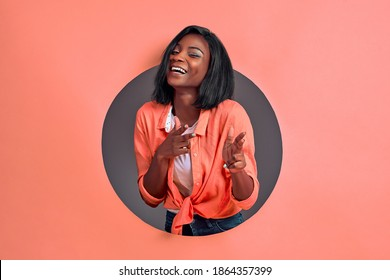 Stunning young woman in casual shirt posing isolated in a circle hole in coral background. People lifestyle concept. Copy space. Point fingers on camera.