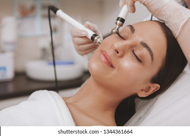 Stunning young woman with flawless skin enjoying facial treatment at cosmetology clinic. Relaxed beautiful female patient visiting dermatologist, getting microcurrent face therapy