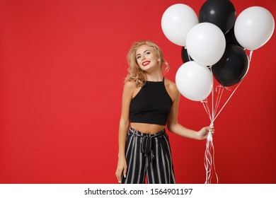 Stunning young woman girl in black clothes posing isolated on bright red wall background in studio. New Year 2020 birthday holiday party concept. Mock up copy space. Celebrating, holding air balloons